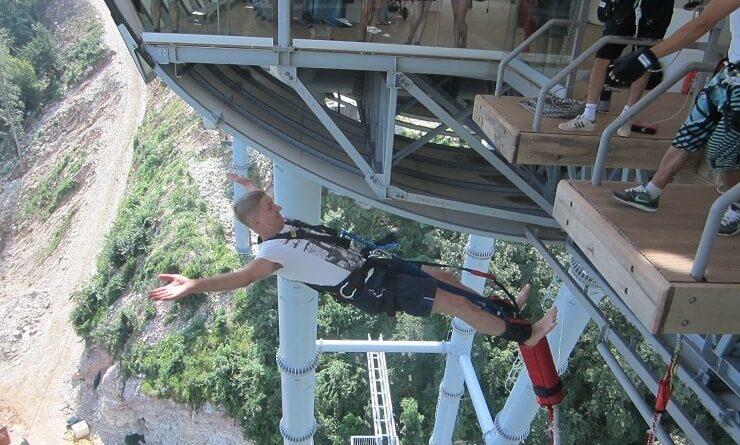 Молодой человек в скай парке совершает прыжок