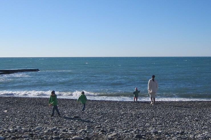 Мама гуляет с детьми у моря