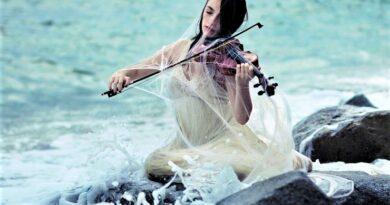 Девушка играет на скрипке на берегу моря