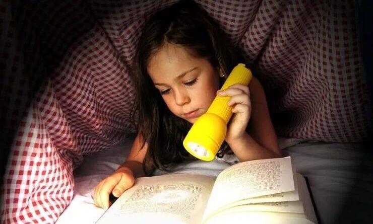 Девочка читает под одеялом